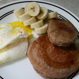 Breakfast consisting of buckwheat pancakes, eggs, and bananas